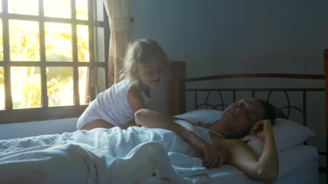 Video Cute little daughter wakes her mother at morning in slow motion.