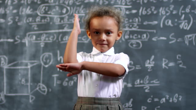 Cute Little Genius Girl Raising her Hand Portrait shot of smart little African-American girl standing before blackboard with complex math formulas and raising her hand genius stock videos & royalty-free footage