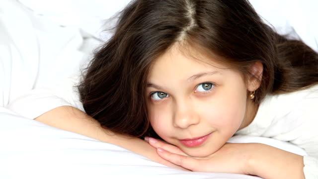 cute little girl 8 years on a bed. - endast en tonårsflicka bildbanksvideor och videomaterial från bakom kulisserna