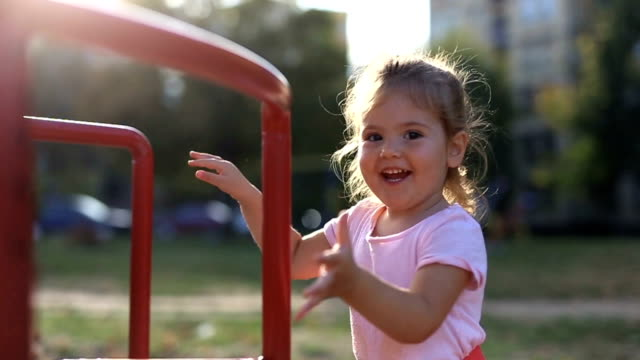 Cute little girl autumn play Cute little girl autumn play outdoor play equipment stock videos & royalty-free footage