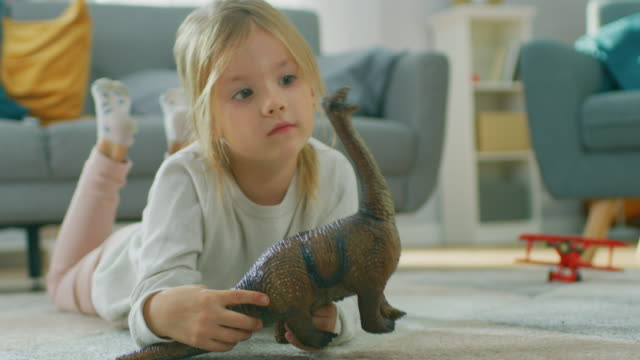 cute little girl blond laying on a carpet at home, plays with toy dinosaurs and airplanes. happy child playing with toys in sunny living room. close-up portrait shot. - dinosaur stock videos and b-roll footage