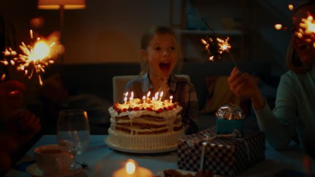 niedliche kleine mädchen feiert geburtstag am esstisch. sie deckt ihre augen und sieht geburtstagskuchen und ist sehr glücklich. glückliches kind, freunde und familie am abend - geburtstagskerze stock-videos und b-roll-filmmaterial