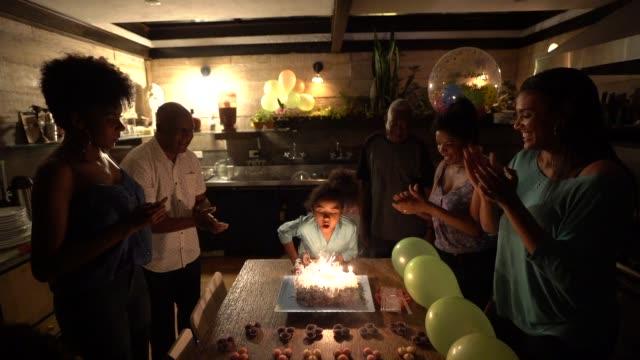 vídeos de stock, filmes e b-roll de bonita menina celebrando festinha de aniversário com a família dela - brigadeiro