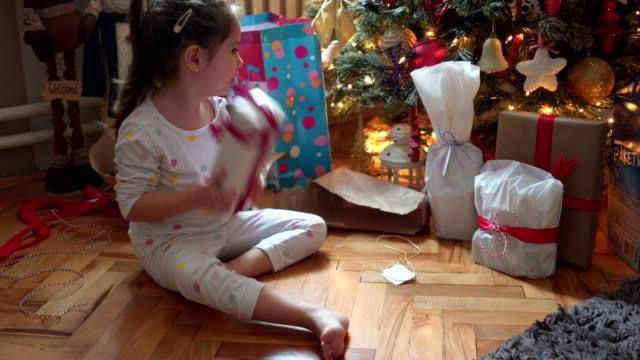 милая маленькая девочка проверяет, что находится в ее подарочной коробке на рождественское утро - трясти стоковые видео и кадры b-roll