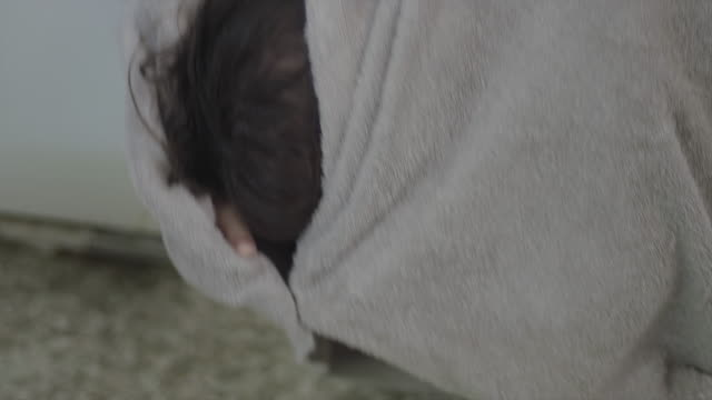 A cute little girl curls up and hides herself in a beach towel A cute little girl curls up and hides herself in a beach towel wearing a towel stock videos & royalty-free footage