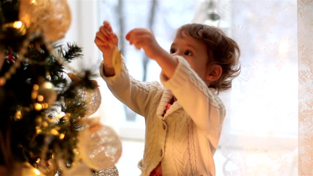 Cute little girl decorates the Christmas tree video