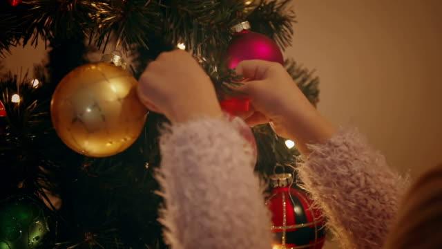 süßes kleines mädchen dekoration weihnachtsbaum - weihnachtsstrumpf stock-videos und b-roll-filmmaterial