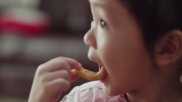 CU : Cute Little Girl Eating A Cookie CU : Cute Little Girl Eating A Cookie, Handheld Shot snack stock videos & royalty-free footage