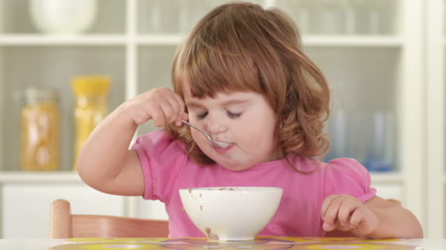 HD: Cute Little Girl Eating Alone With Spoon video
