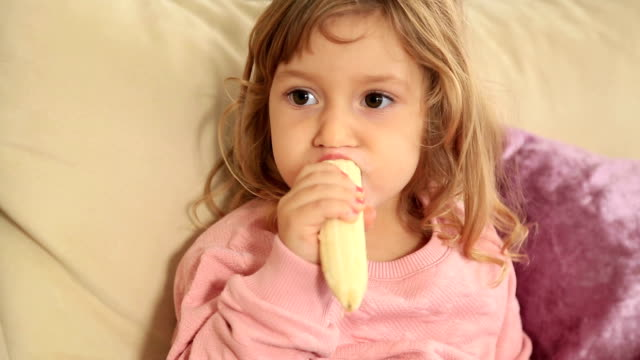 Cute little girl eating banana video