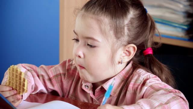 vidéos et rushes de petite fille mignonne mangeant des gaufres croustillantes pendant la pause dans l'école de développement précoce - croustillant