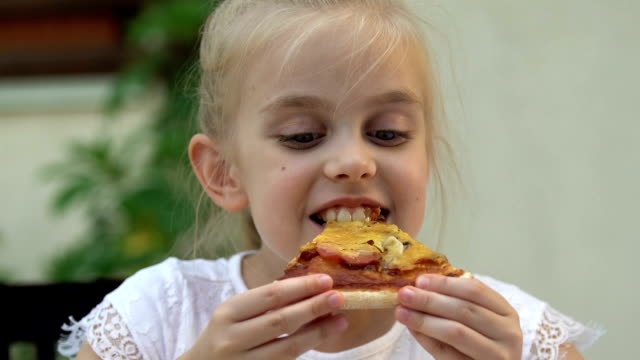 cute little girl eating fresh good tasting pizza, happy childhood, weekend - italian food stock videos & royalty-free footage