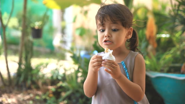 vídeos y material grabado en eventos de stock de linda niña comiendo helado. - ice cream