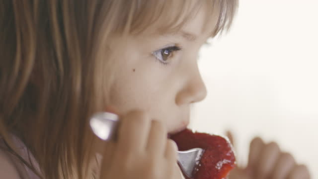 çilek yiyen sevimli küçük kız - dijital yerli stok videoları ve detay görüntü çekimi