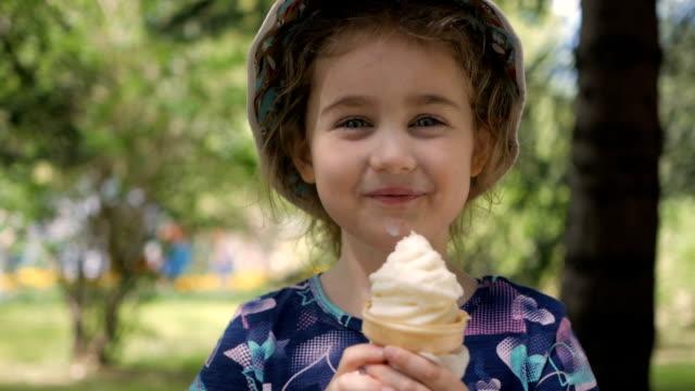 en söt liten flicka åtnjuter en läcker glass kon under sommaren. barn med glass på en promenad i stadsparken - människohuvud bildbanksvideor och videomaterial från bakom kulisserna