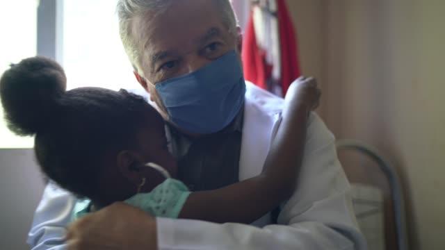 vidéos et rushes de petite fille mignonne examinant le docteur écoutant le battement de coeur - enfant masque