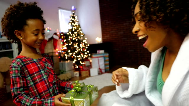Cute little girl gives present to mom on Christmas morning video