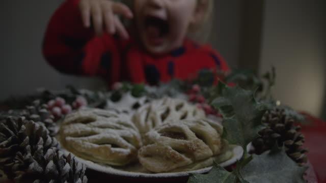 vídeos de stock e filmes b-roll de cute little girl grabbing a tasty christmas pudding when no one is watching - bolo sobremesa