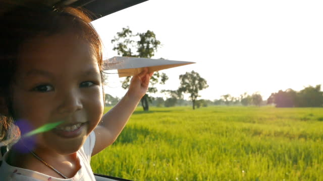 Cute little girl having fun to play with toy paper aircraft out of car window in the countryside. Concept of activity relaxing in evening. Slowmotion shot