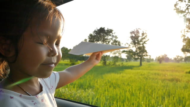 Cute little girl having fun to play with toy paper aircraft out of car window in the countryside. Concept of activity relaxing in evening. Slowmotion shot video