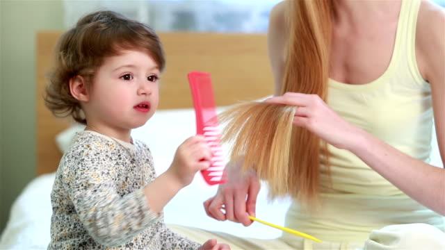 vídeos y material grabado en eventos de stock de linda niña ayuda a su madre toallas su cabello largo, sentado en la cama en el dormitorio. - copiar