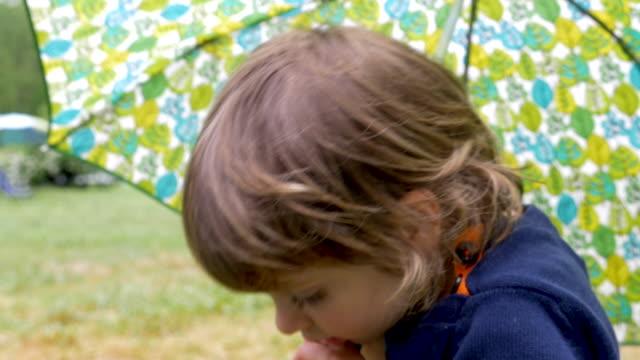 Cute little girl holding an umbrella turns and walks away video