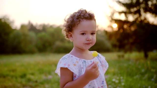 cute little girl holding lollipop - lecca lecca video stock e b–roll