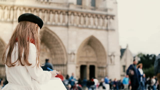 cute little girl in beret sitting in crowded place and drawing. brunette child near the of notre dame in paris, france - paris fashion stock videos & royalty-free footage