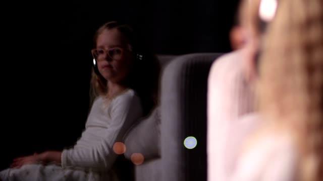 Cute little girl in headphones enjoying music video