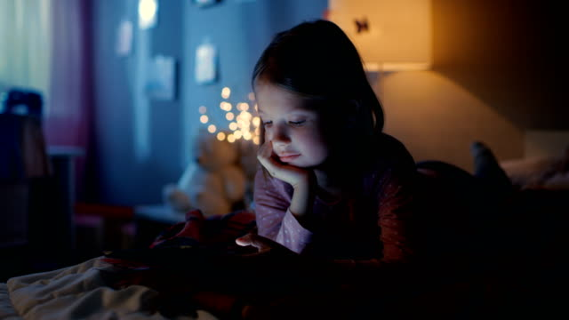 Cute Little Girl in Her Room at Night, Lies on a Bed Uses Smartphone. Her Night Lamp Turned On. video
