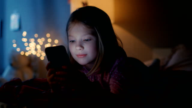 cute little girl in her room at night, lies on a bed uses smartphone. her night lamp turned on. - video call video stock e b–roll