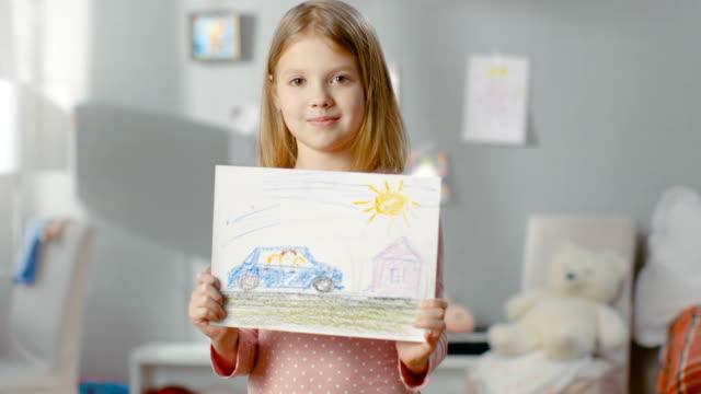vídeos de stock, filmes e b-roll de a menina bonito em seu quarto mostra o desenho de sua família em um carro. - arte e artesanato assunto