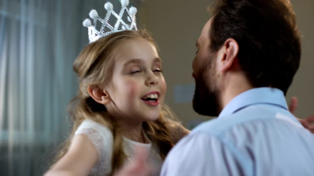 Cute little girl in princess crown dress hugging father, tender relations, party Cute little girl in princess crown dress hugging father, tender relations, party princess stock videos & royalty-free footage