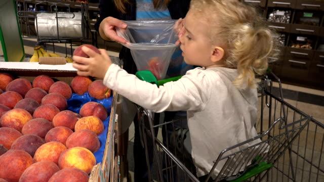 cute little girl in shopping car help mother to pick peach fruits in supermarket - pesche bambino video stock e b–roll