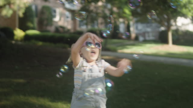 A cute little girl in sunglasses plays with bubbles in her front yard in the summer A cute little girl in sunglasses plays with bubbles in her front yard in the summer pigtails stock videos & royalty-free footage