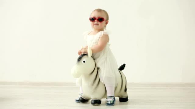 Cute little girl in white dress rocking on inflatable zebra