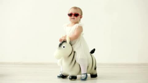 bambina carina in abito bianco dondolarsi in oggetto gonfiabile zebra - carino video stock e b–roll