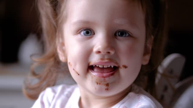 vídeos de stock e filmes b-roll de cute little girl is eating a chocolate and wink to the camera - boca suja