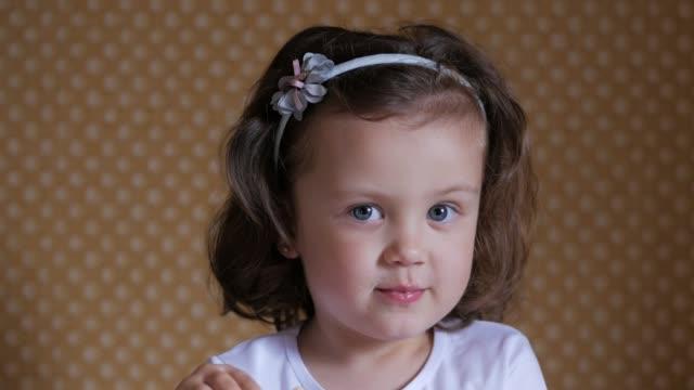 söt liten flicka äter en kakor och blinkning till kameran. konceptet med söt mat och barn. - människohuvud bildbanksvideor och videomaterial från bakom kulisserna