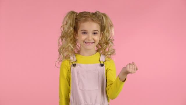 stockvideo's en b-roll-footage met schattige kleine meid nodigt uit om naar haar te komen met haar handen - paardenstaart haar naar achteren