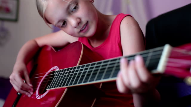 Cute little girl is playing a guitar video