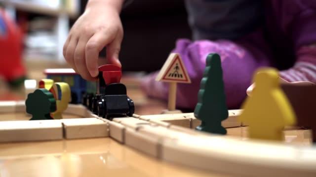 la bambina carina sta giocando con il set di treni in legno - giocattolo video stock e b–roll