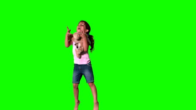 Cute little girl jumping and catching teddy on green screen Cute little girl jumping and catching teddy on green screen in slow motion pigtails stock videos & royalty-free footage