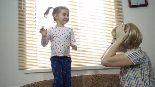 Cute little girl jumping on the bed. Mother calms unruly child. A hyperactive kids. Preschool Education. Cute little girl jumping on the bed. Mother calms unruly child. A hyperactive kids. Preschool Education. obedience stock videos & royalty-free footage