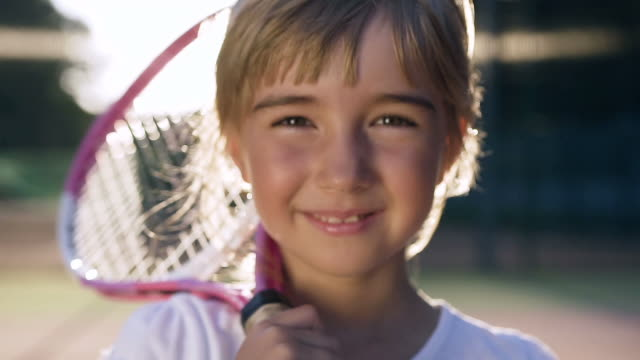 Cute little girl looking to the camera and smiling Cute little girl with tennis racket on the shoulder looking to the camera and smiling. Outdoor shooting. one girl only stock videos & royalty-free footage