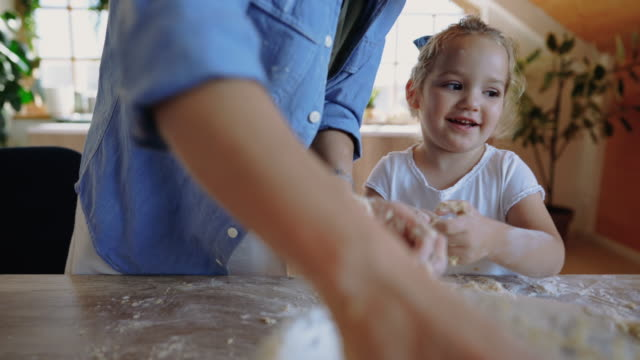 vídeos de stock e filmes b-roll de cute little girl making bread with her mother in the kitchen - baking bread at home