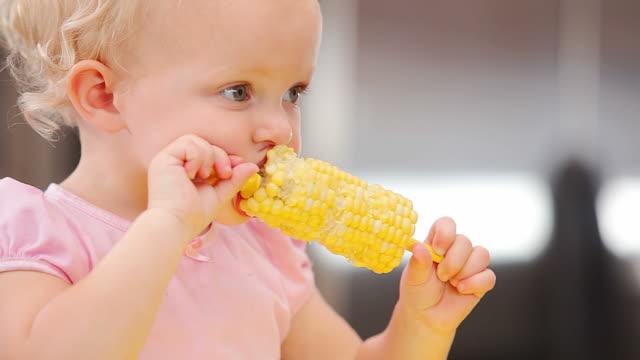 Cute little girl picks at her corn video