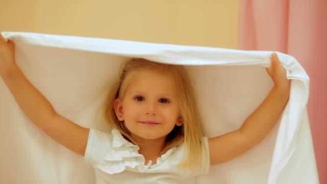 vidéos et rushes de mignonne petite fille jouant avec une couverture - emballé