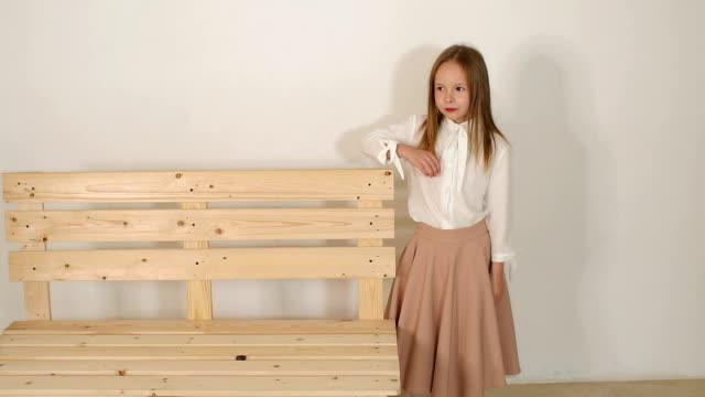 Cute little girl posing in the Studio next to a wooden bench on white background