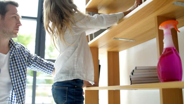 Cute little girl putting books in order while cleaning video